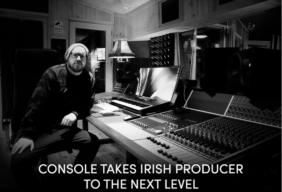 Stuart Gray sitting next to Audient APS8024-HE mixing console in studio